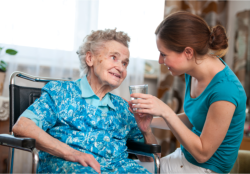 lady giving medicine and water to patient