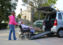 lady pushing patient sitting on a wheelchair to ride on a van